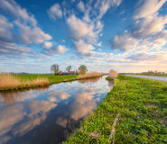 Amazing colorful rustic landscape in Holland. Colorful blue sky with clouds reflected in water, houses near the canal, trees, green grass and yellow reeds at Stock Image