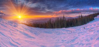 Amazing colorful sunrise in mountains with colored clouds and pink snow on foreground. . Dramatic winter scene with snow.  Stock Image