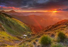 Amazing colorful sunrise in mountains with colored sunrays and fresh grass on foreground. Dramatic colorful scene in mountains Stock Photo