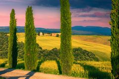 Vitaleta chapel on the hill and grain fields, Tuscany, Italy. Amazing colorful sunset, picturesque Vitaleta chapel Capella di Vitaleta with grain fields at stock photo