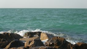 Amazing colorful waves of sea are washing big stones on a breakwater in sunny day stock footage