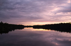 Amazing colors of sunset in Finland. The forest is a silhouette and reflected from the water. Image has some tone effect applied to create more powerful colors Stock Image