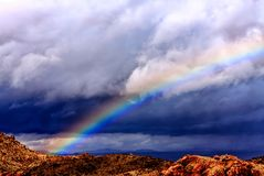 Deep Rainbow Under Dark Clouds. Amazing contrasting rainbow in the desert valley at Joshua Tree National Park Royalty Free Stock Images