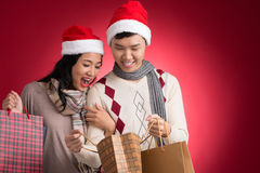 Amazing. Copy-spaced image of a young amazing couple with paperbags full of presents over a red background stock images