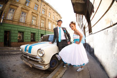 Amazing couple posing by the car on background lviv Stock Photos