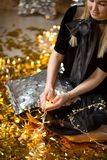 Amazing cute lady celebrating new year birthday party, posing in gold shine background and throwing colorful confetti with silver royalty free stock photography