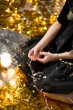Amazing cute lady celebrating new year birthday party, posing in gold shine background and throwing colorful confetti with silver stock images