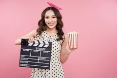 Amazing cute young pretty girl holding clapper board and smiling Stock Photos