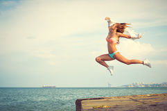 Amazing dancer in swimwear jumping up high on Royalty Free Stock Photos