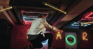 Amazing dark cafe with color lights , young men dancing on the bar table. red epic stock footage
