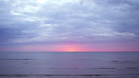 Amazing dark scenic vivid crimson rare red sunset with violet and magenta colors at the Baltic Sea with small sun at the stock footage