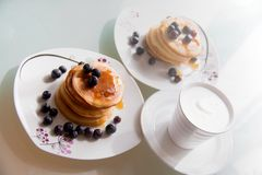 Homemade pancake plates topped by maple syrup, cinnamon and blueberries on white plates with cup of delicious coffee with cream royalty free stock image