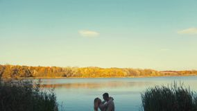 Amazing, distant view of a young couple kissing each other by the riverside. Love story, forever together. Just married stock video