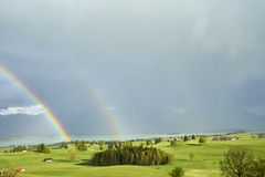 Amazing double rainbow over lush farmlands in the foothills of the Bavarian Alps with Forggensee and Neuschwanstein Castle in the. The most wonderful place to royalty free stock photos