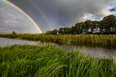 Amazing double rainbow over the small river. Stock Photos