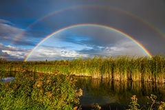 Amazing double rainbow over the small river. Stock Photo