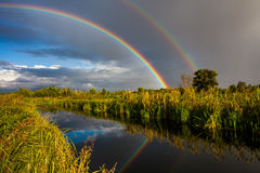 Amazing double rainbow over the small river. Royalty Free Stock Photos