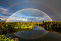 Amazing double rainbow over the small river. Stock Images