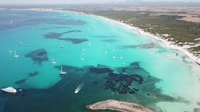 Amazing drone aerial landscape of the charming beach Es Trencs and the boats with a turquoise sea. It has earned the reputation of Caribbean beach of Mallorca stock video footage
