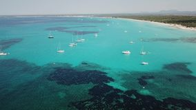Amazing drone aerial landscape of the charming beach Es Trencs and the boats with a turquoise sea. It has earned the reputation of Caribbean beach of Mallorca stock footage