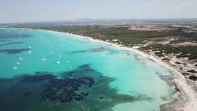 Amazing drone aerial landscape of the charming beach Es Trencs and the boats with a turquoise sea. It has earned the reputation of Caribbean beach of Mallorca stock video