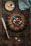 Amazing Easter cake with chocolate and colourful Easter eggs on dark background. Top view. Selective focus. Copy space stock images