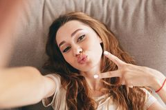 Amazing emotional pretty lady make selfie make peace gesture. Image of young amazing emotional pretty lady lies on sofa indoors. Looking camera make selfie make royalty free stock photo