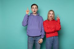 Amazing emotional young couple friends in casual clothes posing with open mouth pointing up with fingers royalty free stock photography