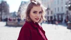 Amazing European girl with a perfect figure showing her belly to camera, but then playfully hides it with a red coat. Urban settings on the background. Close stock video