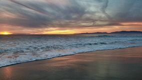 Amazing evening sky over the sand 4k. Early sunset on beach over the ocean surf 4k Stock Photography