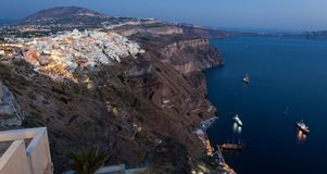 Amazing evening view of Fira with cruise ships royalty free stock photo
