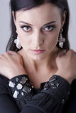 Amazing eyes woman with arms crossed, close up portrait. Close up portrait of beautiful feminine woman with decorative sparkling stones on her sleeves and silver Royalty Free Stock Images