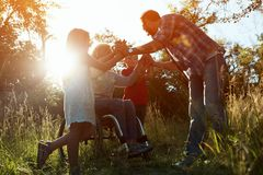 Woman in an armchair has fun with her husband and two children in park stock photography