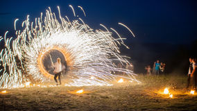 Amazing Fire Show with a fireworks. O-shape full-round line with a lot of sparks. And rapt admirative audience around. Beautiful wedding night in Carpathian Stock Photography