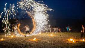 Amazing Fire Show with a fireworks. U-shape half-round line with a lot of sparks. And rapt admirative audience around. Royalty Free Stock Image