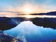Amazing fire sunrise on the sea bay, rocky shore. Hot sunset at rocky horizon royalty free stock photography