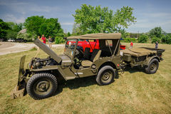 Amazing front and side view of classic vintage military vintage jeep with a small trailer Royalty Free Stock Photos