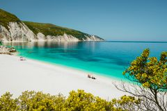 Amazing Fteri beach lagoon, Cephalonia Kefalonia, Greece. Tourists under umbrella relax near clear blue emerald turquise stock photo