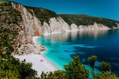 Amazing Fteri beach lagoon, Kefalonia, Greece. Tourists under umbrella chill relax near clear blue emerald turquoise sea royalty free stock images