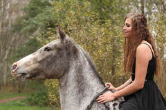 Amazing girl with long hair riding a horse stock photography