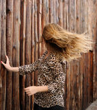 Amazing girl in motion hair. Amazing girl in motion on the background of wooden fence, blonde hair Stock Images