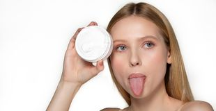 Amazing girl with natural perfect skin with bare shoulders hide one eye with cream tube, shows tongue. Studio photo on stock images
