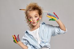 Beautiful little girl with a painted hands and cheeks is posing on a gray background. Amazing girl with a painted cheeks having a brush in her stylish hairstyle stock photo