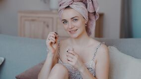 Amazing girl sits on the sofa with towel on her head, dresses up for party and makes pedicure gel nail polish slow
