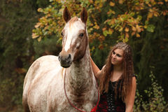 Amazing girl standing next to the appaloosa horse Royalty Free Stock Photo