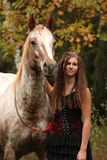 Amazing girl standing next to the appaloosa horse Stock Images