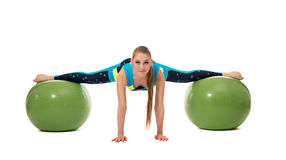 Amazing girl stretched out on two fitness balls Royalty Free Stock Images