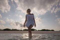 Amazing girl in white beach dress is walking in the sea Royalty Free Stock Photo