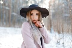 Amazing glamorous pretty beautiful young woman in a luxurious black hat in a stylish pink warm coat posing on a sunny day. In a winter park. fashionable girl on stock photos