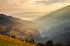 Amazing glowing sunrise in mountains. Countryside in fall colors. village down in the valley in haze and fog stock photo